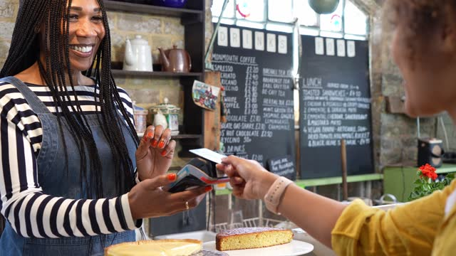 woman paying for gift with credit card in coffee shop