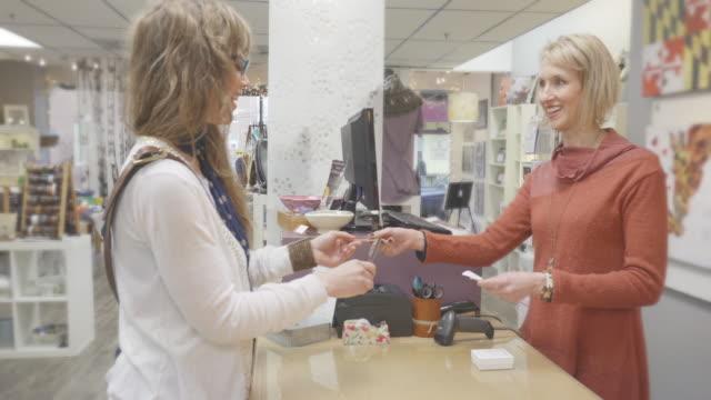 女性がレジの机で商品代金 - ギフトショップ点の映像素材/bロール