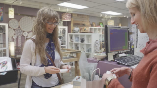 woman paying for items at cashier's desk - weekend activities stock videos & royalty-free footage