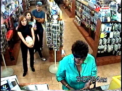 HA WS Woman paying for items in convenience store while other customers wait in line in behind her / Brooklyn, New York, USA