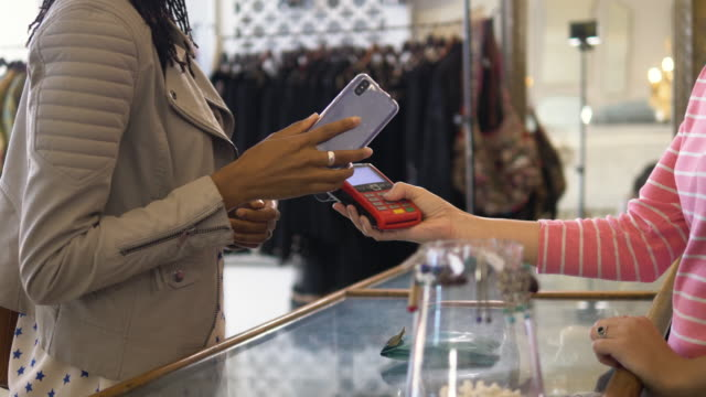 vidéos et rushes de woman paying for jewelry with contactless payment technology in a clothes store - boutique