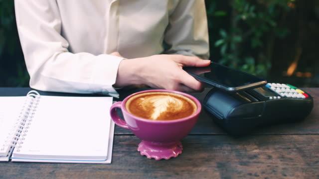 frau zahlt über smartphone mit nfc-technologie in cafe - bank stock-videos und b-roll-filmmaterial