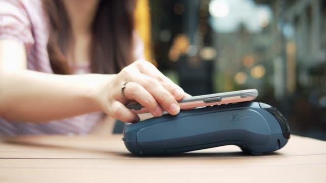 vídeos y material grabado en eventos de stock de mujer pagando a través de un teléfono inteligente usando tecnología nfc en cafe - pago por móvil