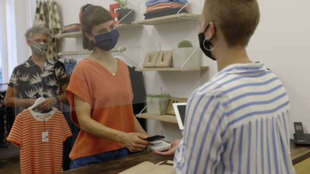 woman paying using her mobile phone in the clothing store - clothes shop stock videos & royalty-free footage