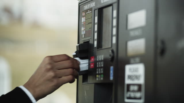 CU Woman paying with credit card at gas station / Orem, Utah, USA
