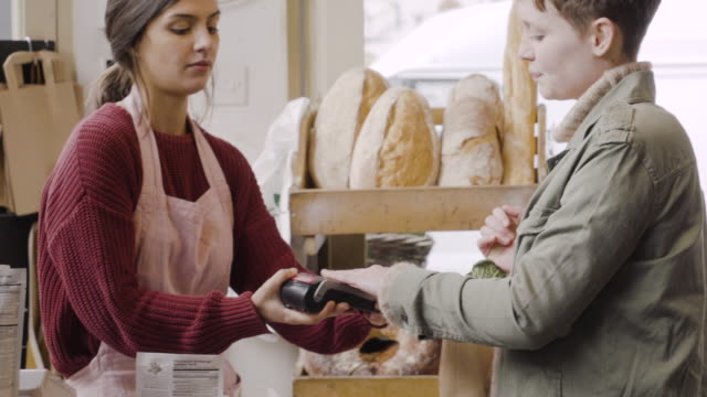 Woman pays contactless on card reader machine, offered by cashier in delicatessen shop.