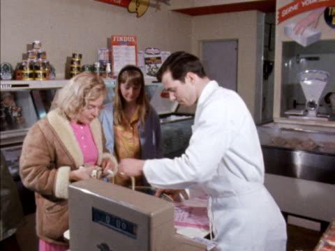 vídeos de stock e filmes b-roll de a woman pays for groceries in a supermarket 1968 - vendas