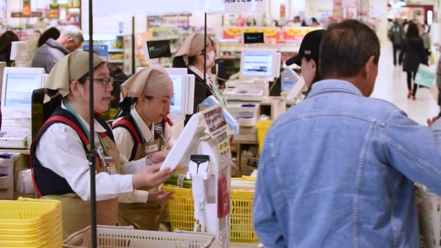 A woman pays for purchases at the checkout counter at a supermarket inside the Ito Yokado Co Ario shopping center owned by Seven i Holdings Co during...