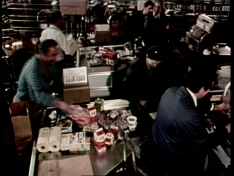a woman pays the cashier for purchased groceries as a bagger packs the goods - bagger stock videos & royalty-free footage