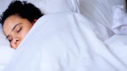 Woman peacefully sleeping on bed 4k