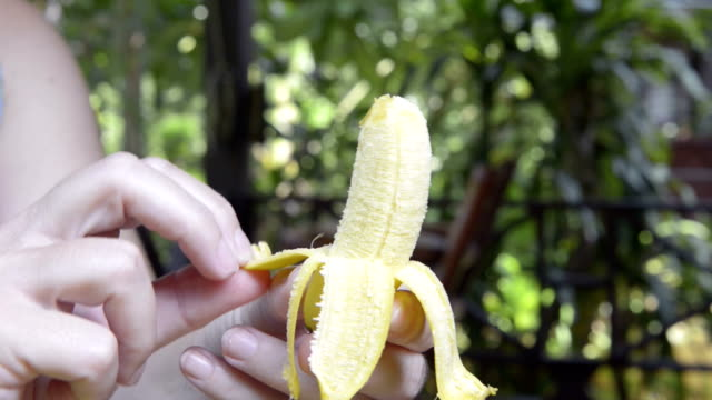 stockvideo's en b-roll-footage met woman peeling a finger banana - schil