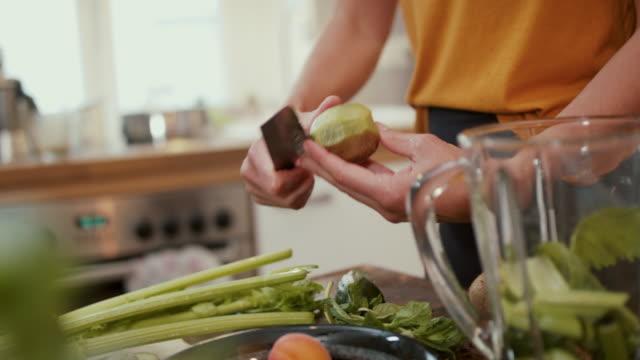 woman peeling kiwi fruit in kitchen at home - smoothie stock videos & royalty-free footage