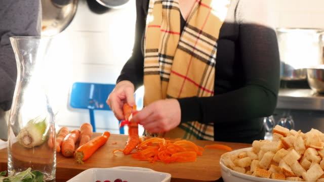 CU Woman peeling organic carrots during cooking class with friends