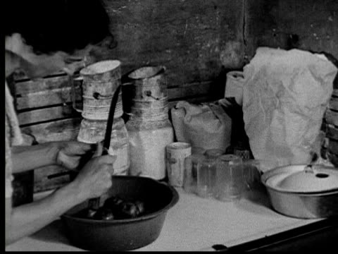 1935 b/w cu woman peeling potatoes with knife / usa - stereotypical homemaker stock videos & royalty-free footage