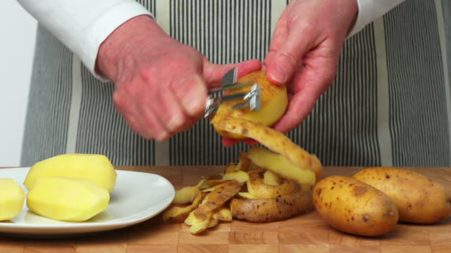 woman peeling potatos close-up (4:2:2@100 mb/s) - peel plant part stock videos and b-roll footage