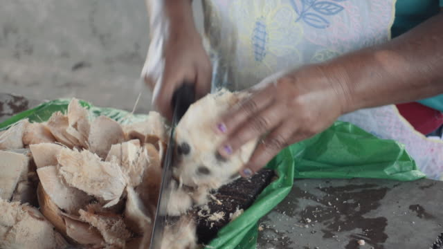 Woman peels coconut in Nicaragua using a big knife. In this 4K video we can see the hands of a native from Central America cutting the skin of this exotic fruit with energy in the market of Masaya.