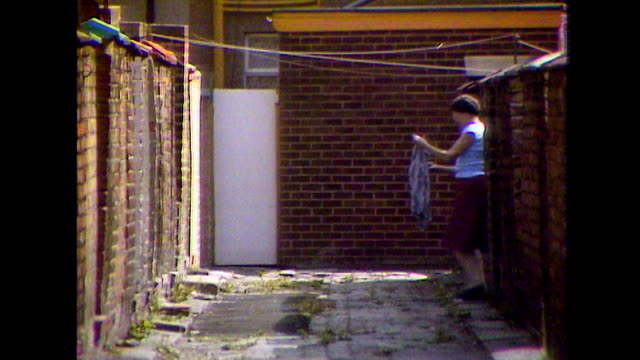 woman pegs out washing on line in alley; 1984 - gender stereotypes stock videos & royalty-free footage
