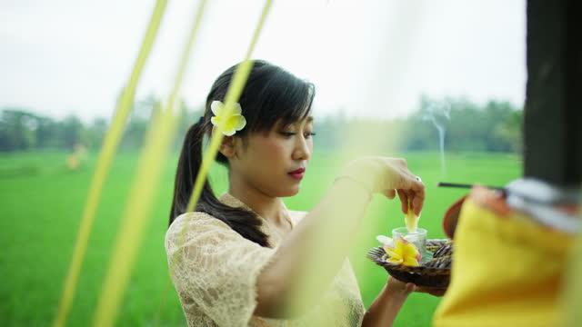 vídeos de stock e filmes b-roll de woman performing canang sari daily religious offering indonesia - benção