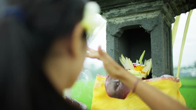 vídeos de stock e filmes b-roll de woman performing canang sari daily spiritual ritual indonesia - benção
