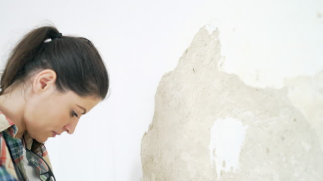woman performing contruction works in the house. - plaster stock videos and b-roll footage