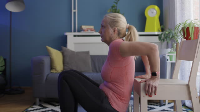 woman performing exercise with a chair at home - mature women stock videos & royalty-free footage