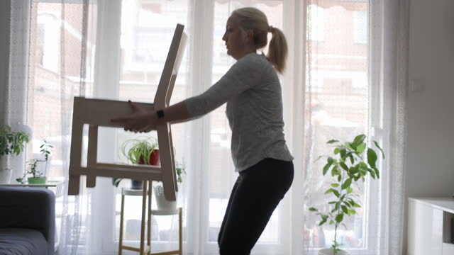 vídeos de stock e filmes b-roll de woman performing exercise with a chair at home - cadeira