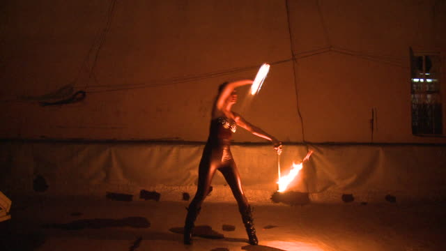 WS Woman performing fire dance with illuminated sticks, New York City, New York, USA