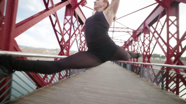 vídeos de stock e filmes b-roll de woman performing gymnast rhythmic jump at outdoors - body de ginástica