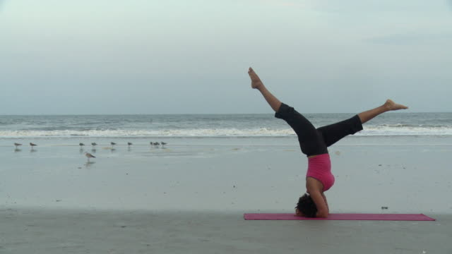 WS Woman performing headstand on beach / Jacksonville, Florida, USA