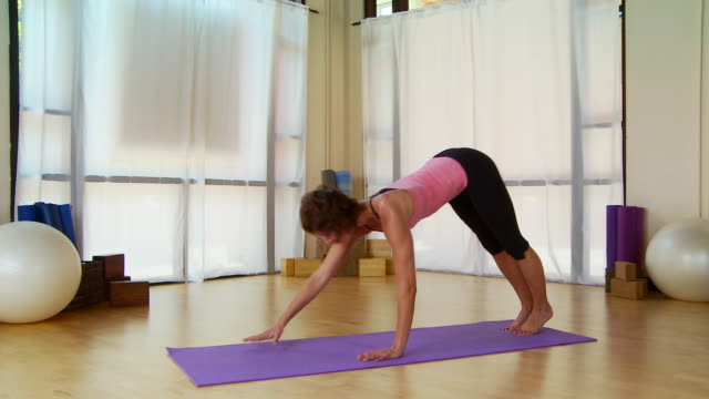woman performing pilate move on a mat - bodyweight training stock videos & royalty-free footage