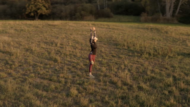 vídeos de stock, filmes e b-roll de woman performing yoga in green field at sunset - pose de arvore