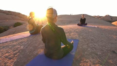 vídeos y material grabado en eventos de stock de mujer realiza la pose del árbol de yoga al atardecer en moab - vriksha asana