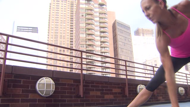 woman performs lunging exercises on a rooftop on august 22 2013 in new york new york - hampelmannsprung stock-videos und b-roll-filmmaterial
