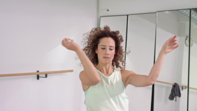 stockvideo's en b-roll-footage met woman performs modern dance in a dance studio / dance teacher / professional dancer - dance studio