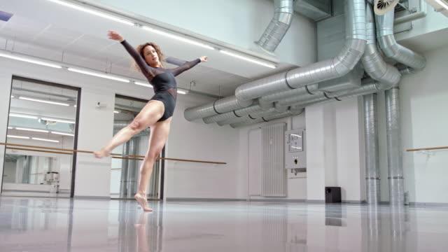woman performs modern dance in a dance studio / dance teacher / professional dancer