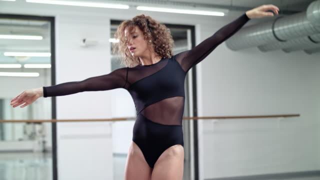 vídeos de stock, filmes e b-roll de woman performs modern dance in a dance studio / dance teacher / professional dancer - dance studio