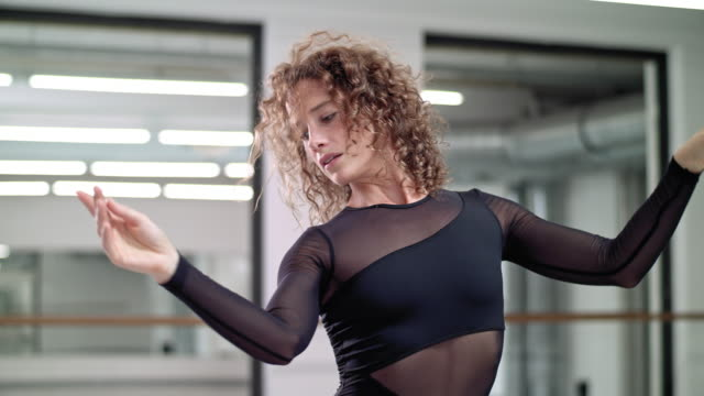 vídeos de stock, filmes e b-roll de woman performs modern dance in a dance studio / dance teacher / professional dancer - cabelo de comprimento médio