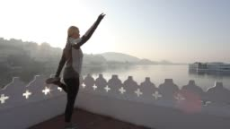 Woman performs stretching exercises above lake and floating palace at sunrise