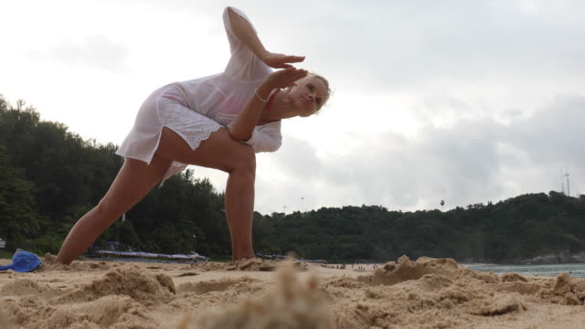 woman performs yoga moves on beach - only mature women stock videos & royalty-free footage