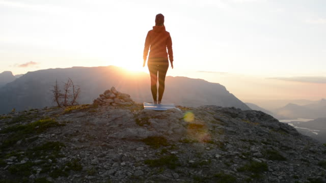 Woman performs yoga moves on mountain summit, sunrise
