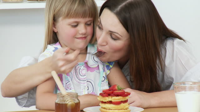 CU Woman persuading daughter (4-5) to eat pancakes / Cape Town, Western Cape, South Africa