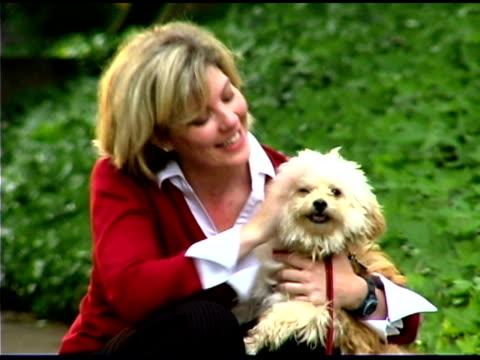 stockvideo's en b-roll-footage met woman petting dog outdoors - alleen één mid volwassen vrouw