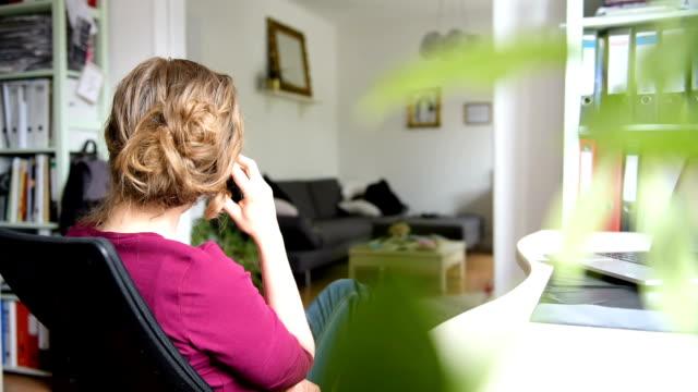 vídeos y material grabado en eventos de stock de mujer llamar a un teléfono desde su casa en un escritorio de oficina en la sala de estar. - teléfono con cable