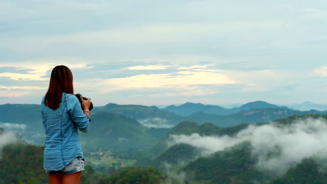 Woman photographer taking photo at mountain, Slow motion