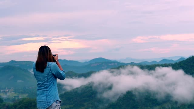 woman photographer taking photo at mountain, slow motion - freelance work stock videos & royalty-free footage