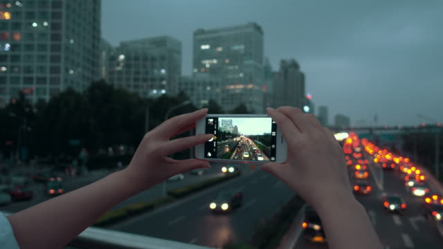 Woman photographing city night using phone