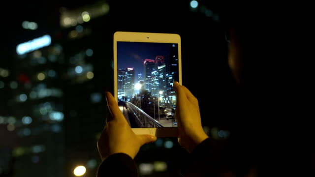 Woman photographing city night using tablet