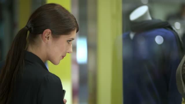 vídeos de stock, filmes e b-roll de hd: mulher fotografando roupas na vitrine - olhando vitrines