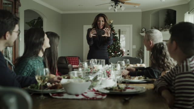 woman photographing family at christmas dinner then posing for cell phone selfie / orem, utah, united states - photographing video stock e b–roll