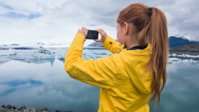 woman photographing floating icebergs in glacial lake with smartphone - lagoon stock videos and b-roll footage